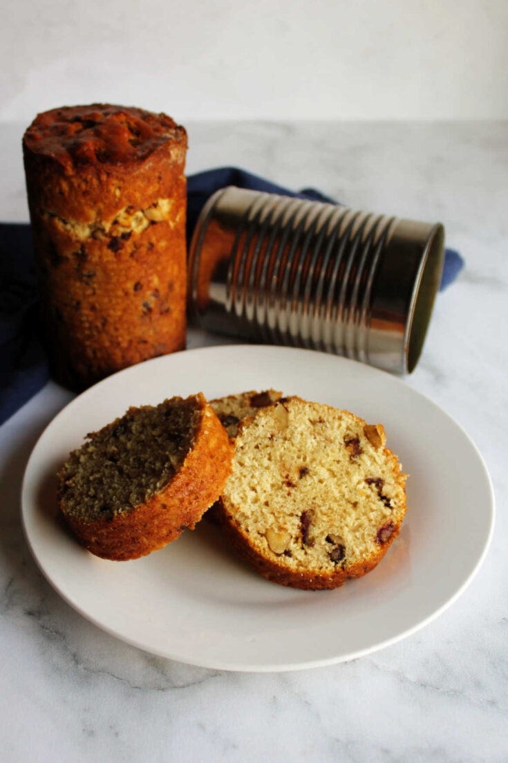 slices of date nut bread on plate next to loaf of bread and empty tin can.