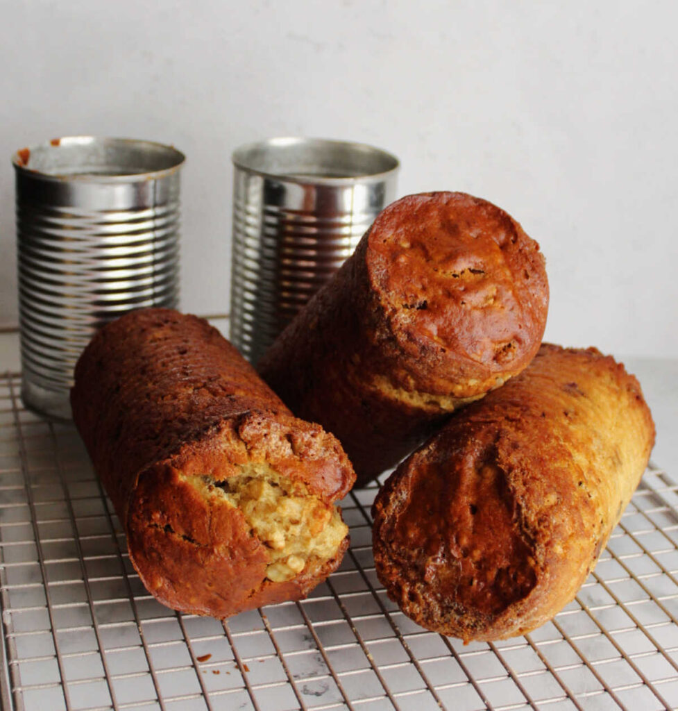 can shaped date nut bread cooling on wire rack with cans in background.