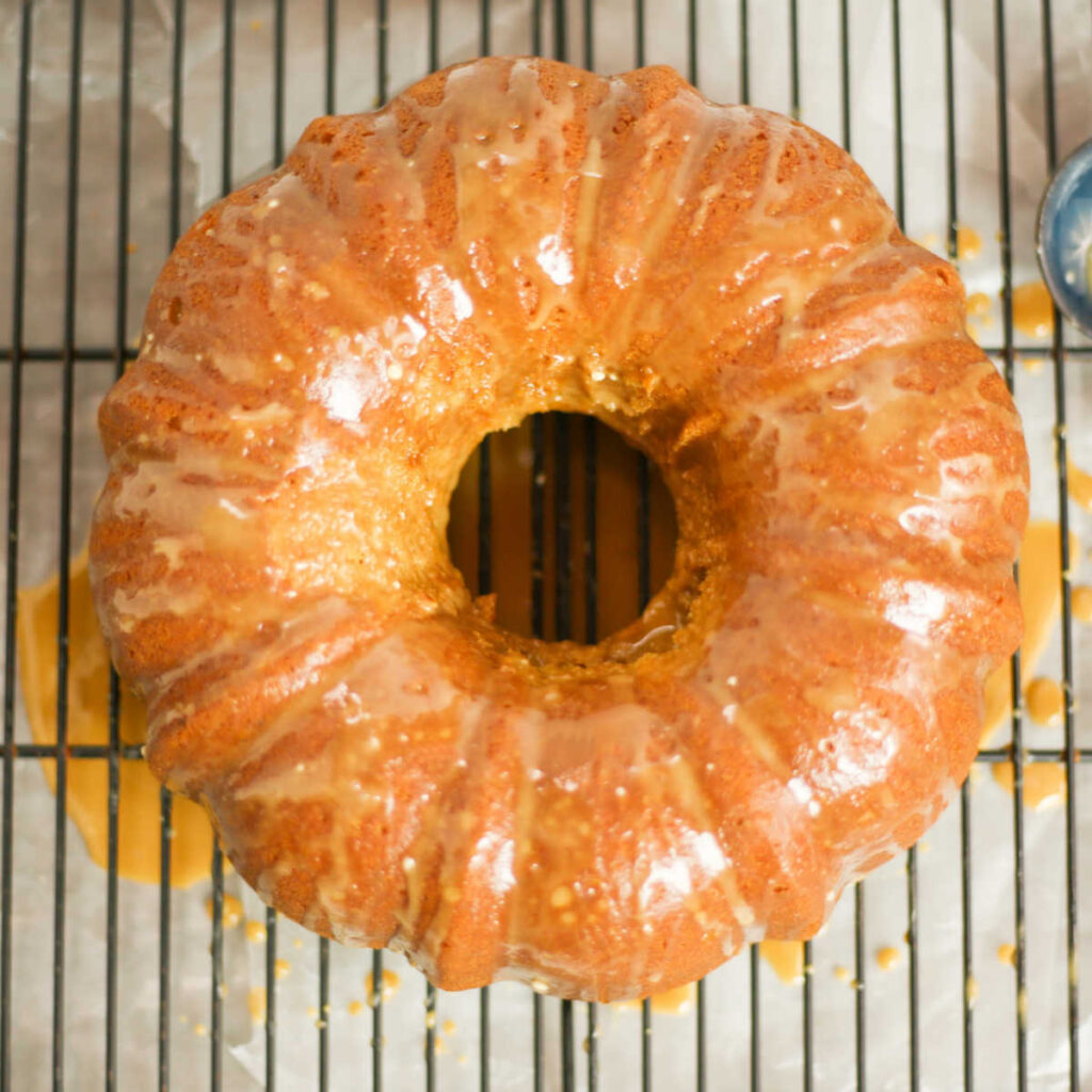 Freshly glazed chai bundt cake on rack for drips.