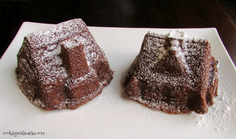 small gingerbread house cakes with powdered sugar snow on roof.