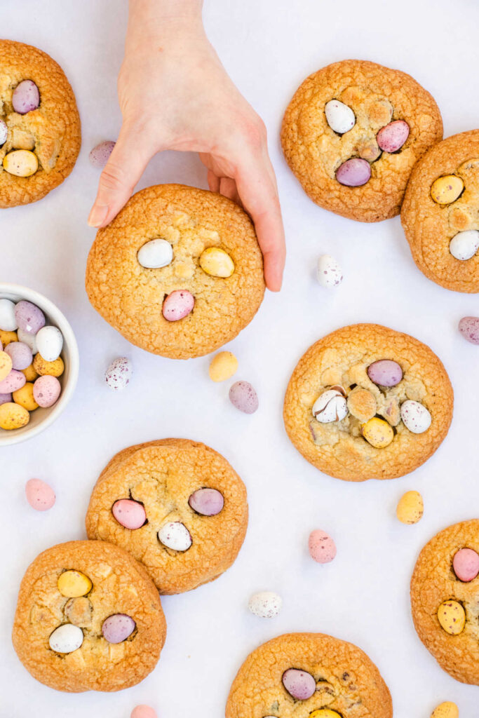 Hand holding large golden brown cookie with mini chocolate eggs on top.