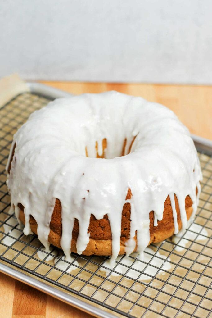 lemon bundt cake with white lemon ginger glaze dripping through cooling rack onto cookie sheet.