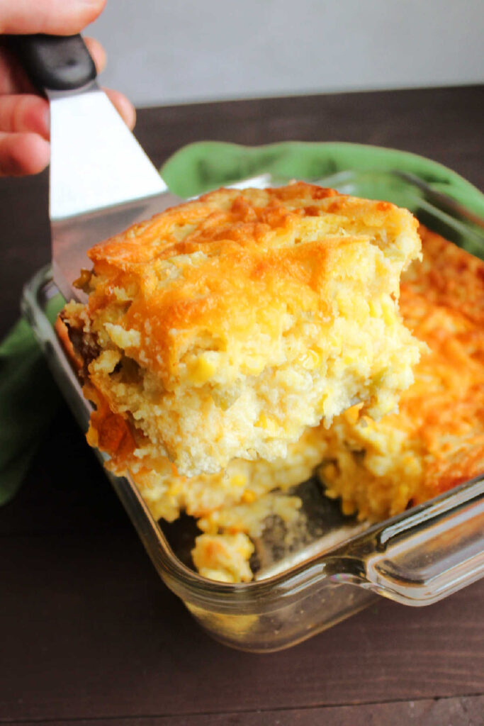 spatula lifting out slice of chili cheese corn casserole showing soft interior.