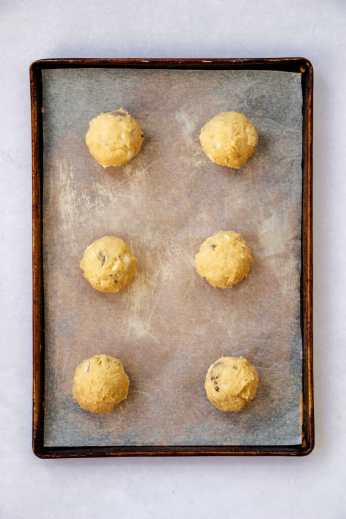 Large scoops of cookie dough on pan, ready to bake.