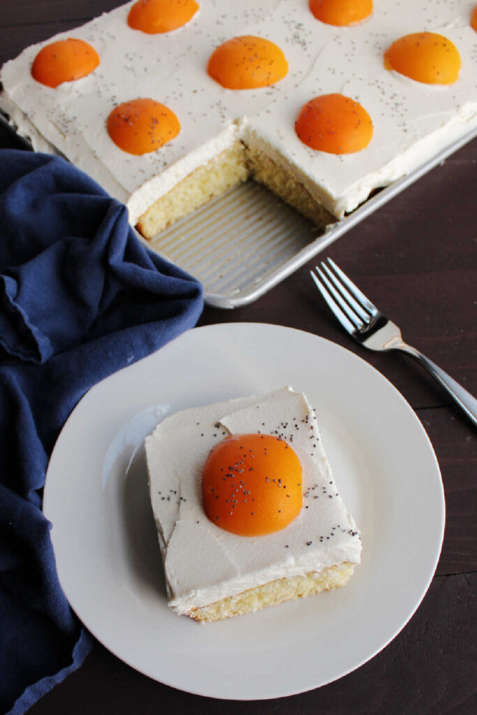 slice of cake that looks like a sunny side egg in front of remaining sheet cake decorated with several apricot egg yolks.
