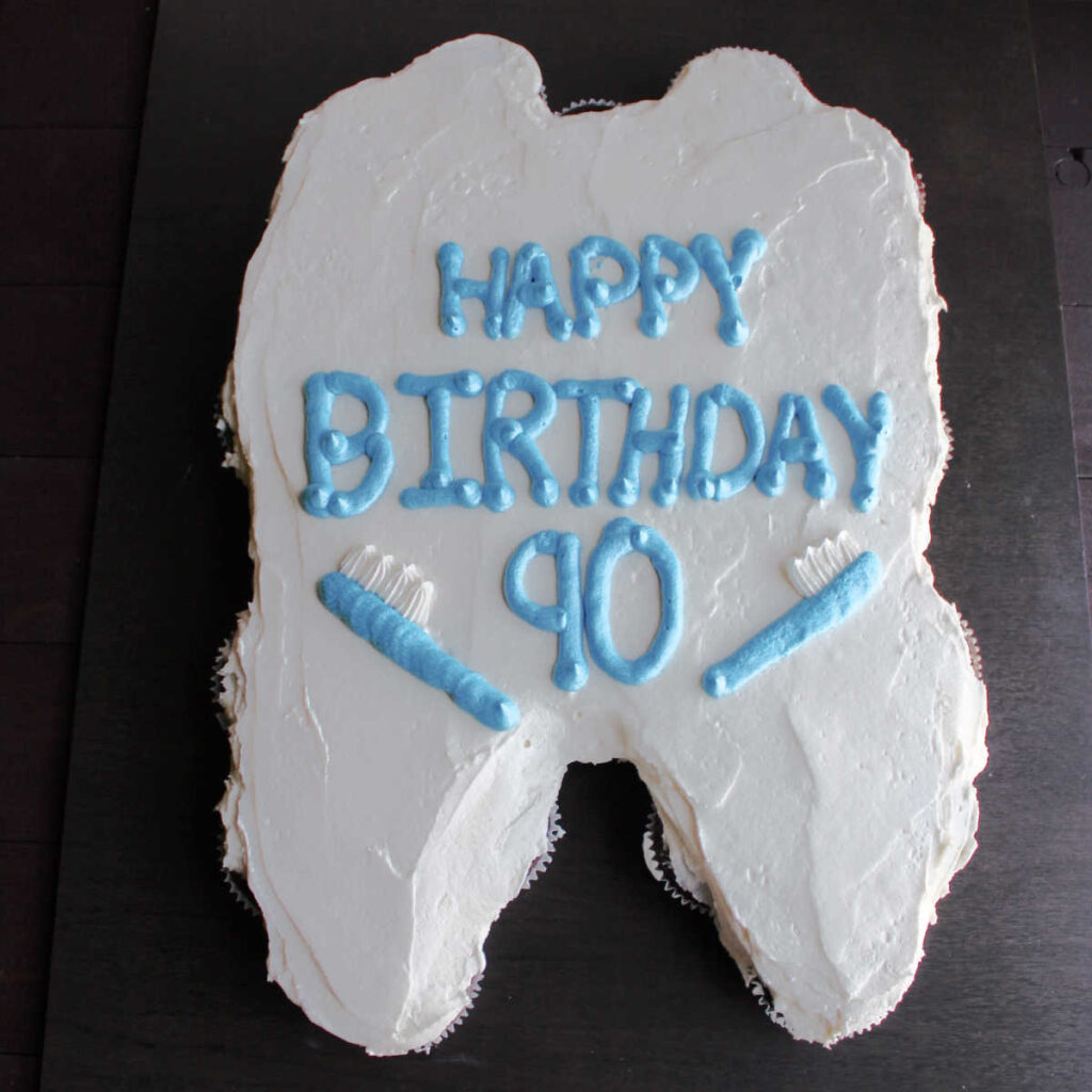 cupcake pull apart cake in the shape of a tooth with happy birthday and toothbrushes piped on in frosting.