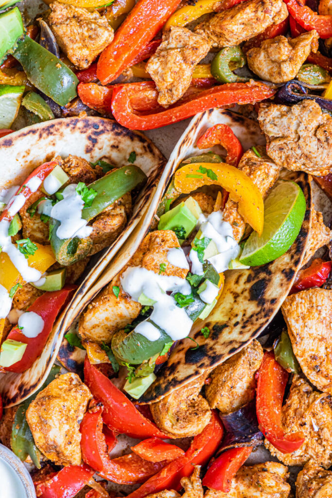 sheet pan chicken fajitas in tortillas with sour cream, lime wedges and cilantro.