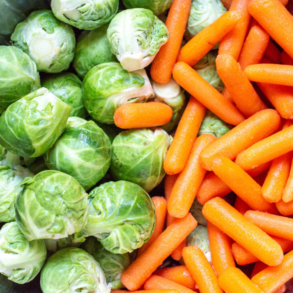 fresh Brussels sprouts and carrots next to each other.