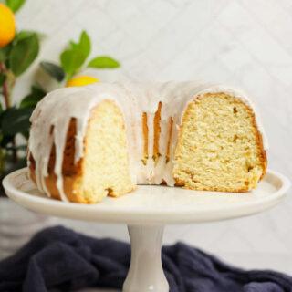 2/3 of lemon bundt cake with white glaze and soft yellow interior showing.