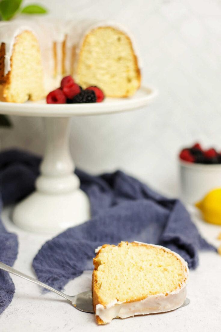 Slice of lemon bundt cake with remaining cake in background.