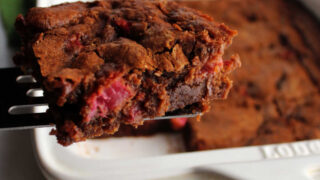 Lifting first slice of rhubarb brownies out of pan.