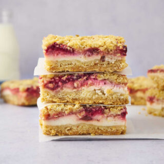 Stack of crumb bars with strawberries and yogurt in the middle.