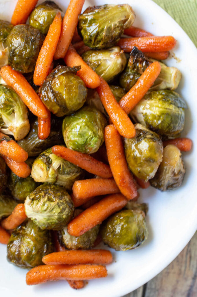 Serving bowl filled with honey roasted carrots and brussels sprouts.