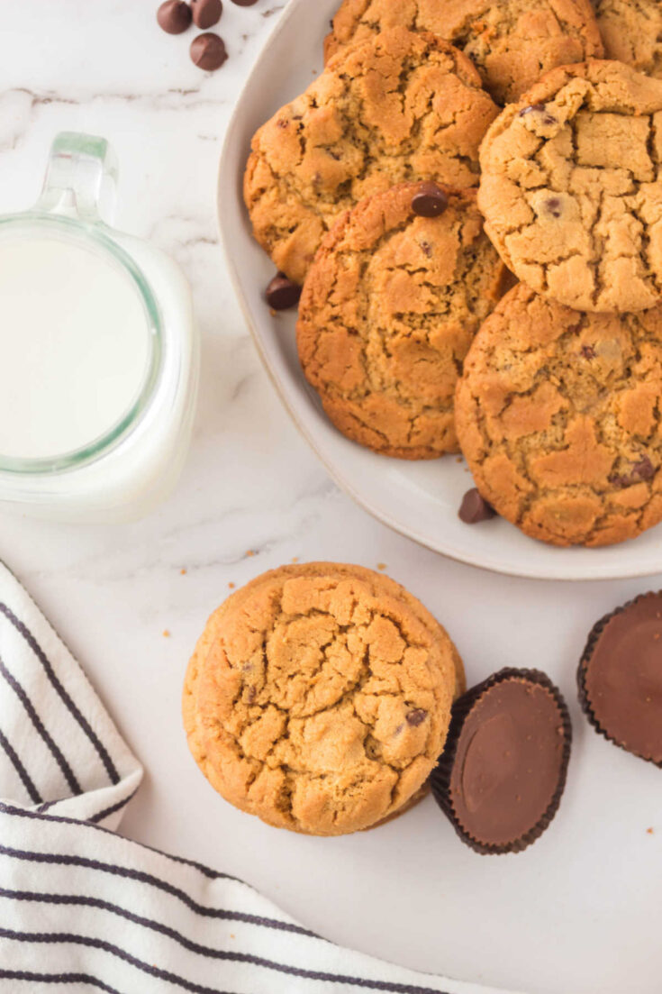 chewy peanut butter chocolate chip cookies with glass of milk and Reese's peanut butter cups.