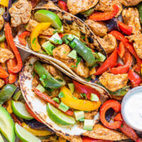 chicken fajita tacos with limes and sour cream.