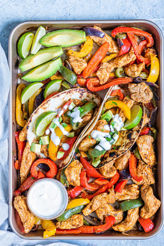 Sheet pan filled with chicken fajita fixings with avocado wedges, limes and sour cream.