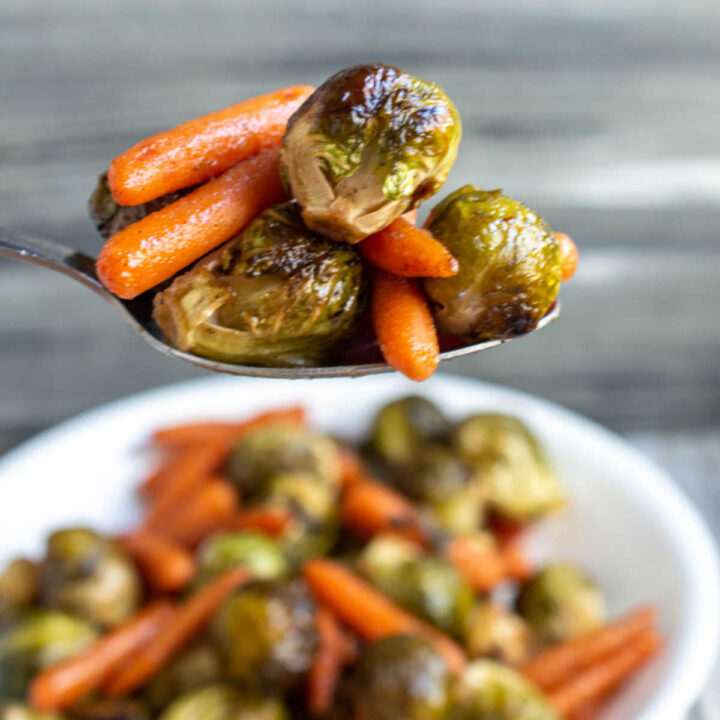 Spoonful of honey roasted brussels sprouts and carrots, ready to eat.