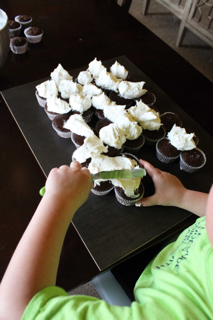 Starting to spread out scoops of frosting over arranged cupcakes.
