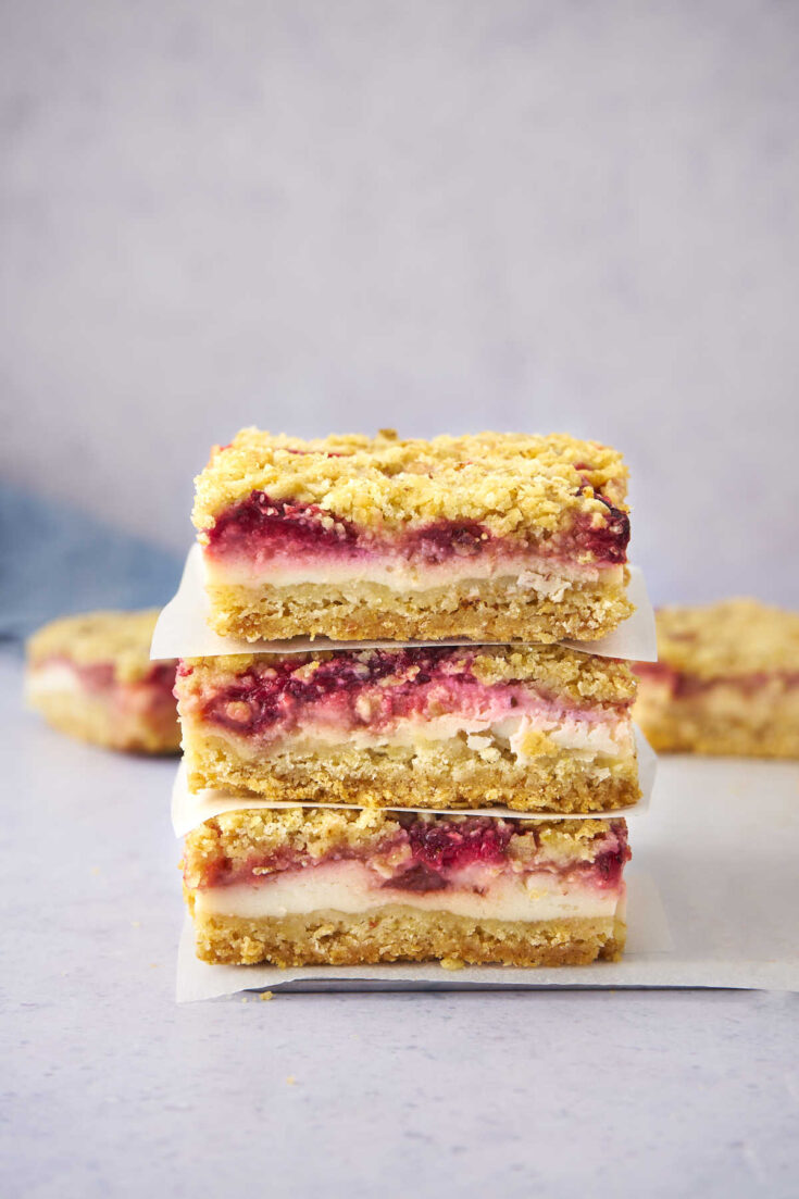 pile of strawberry yogurt crumble bars with sheets of parchment paper.