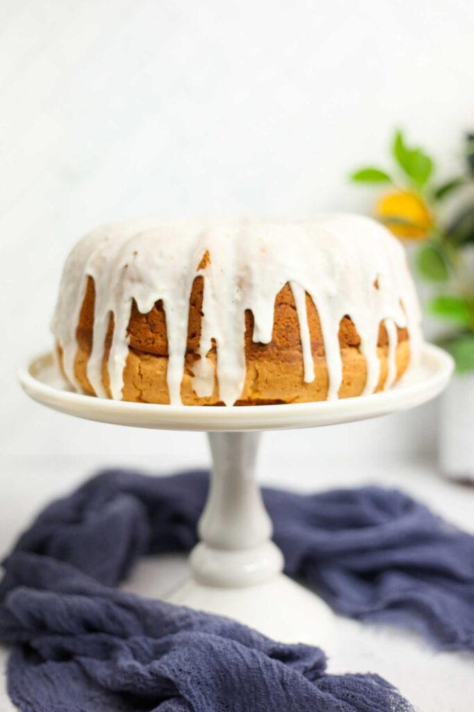 Whole lemon bundt cake with white lemon ginger glaze on top of cake stand.