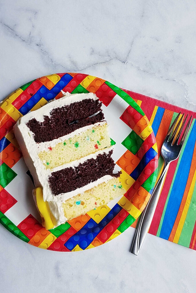 Slice of cake with 4 layers of alternating funfetti and chocolate cake with marshmallow buttercream between the layers. of cake