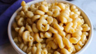 Close bowl of creamy macaroni and cheese with curly noodles.