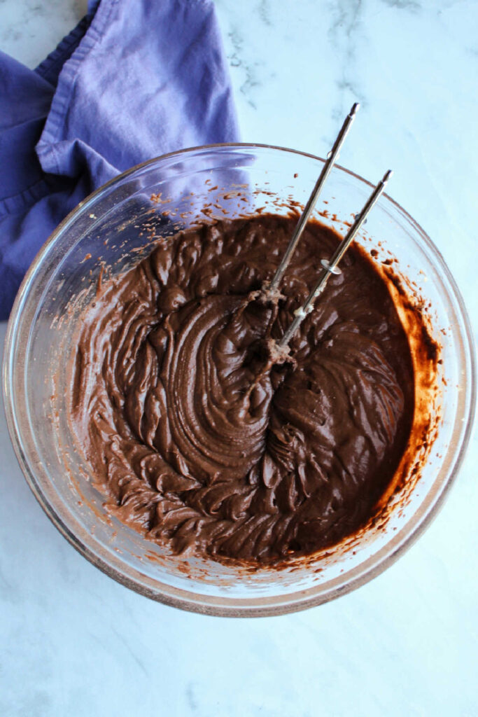 Bowl of chocolate cake batter and mixer beaters.
