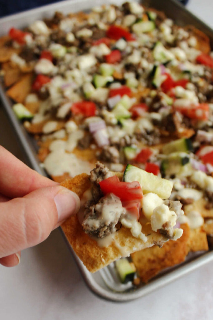 Hand holding pita chip topped with meat, cucumber, tomatoes, feta and tzatziki sauce.