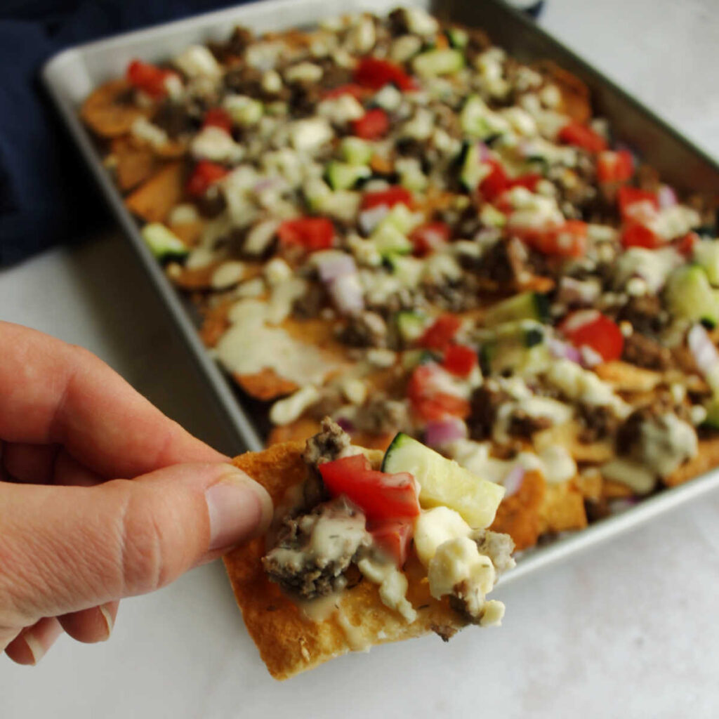 Sheet pan filled with gyro inspired nachos topped with feta, cucumbers, tomatoes, tzatziki and more.