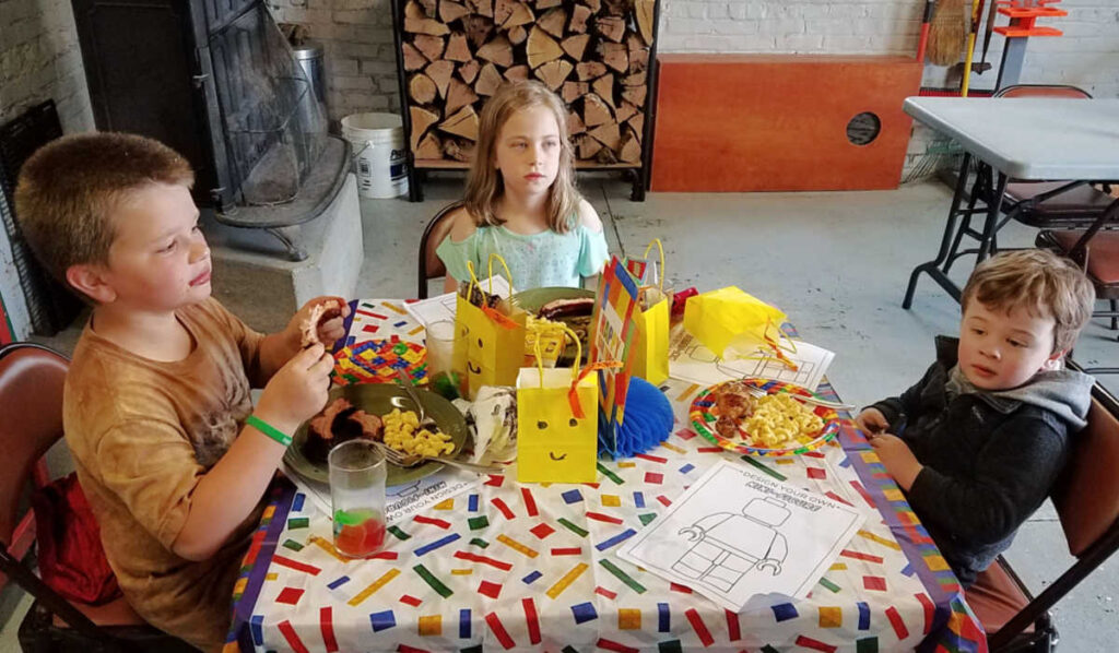 Kids table with Lego coloring sheets, treat bats and kids eating dinner.