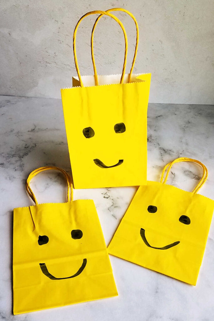 yellow treat bags with faces on them to look like lego heads.