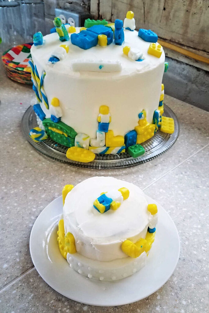 A small and large cake with marshmallow buttercream and decorated with fondant legos.