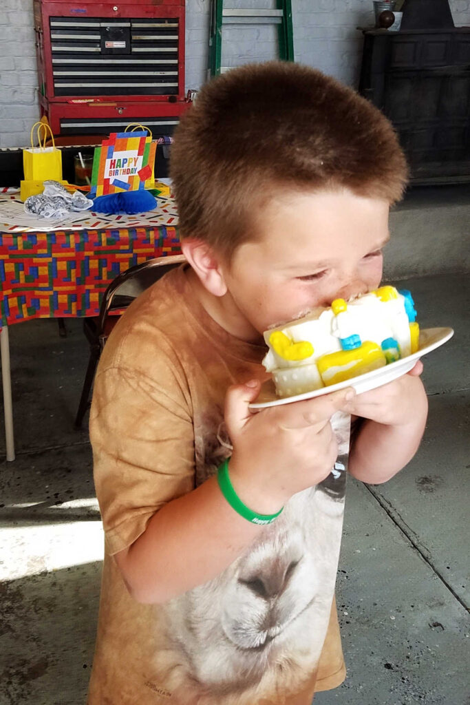 Boy putting his face into a cake.