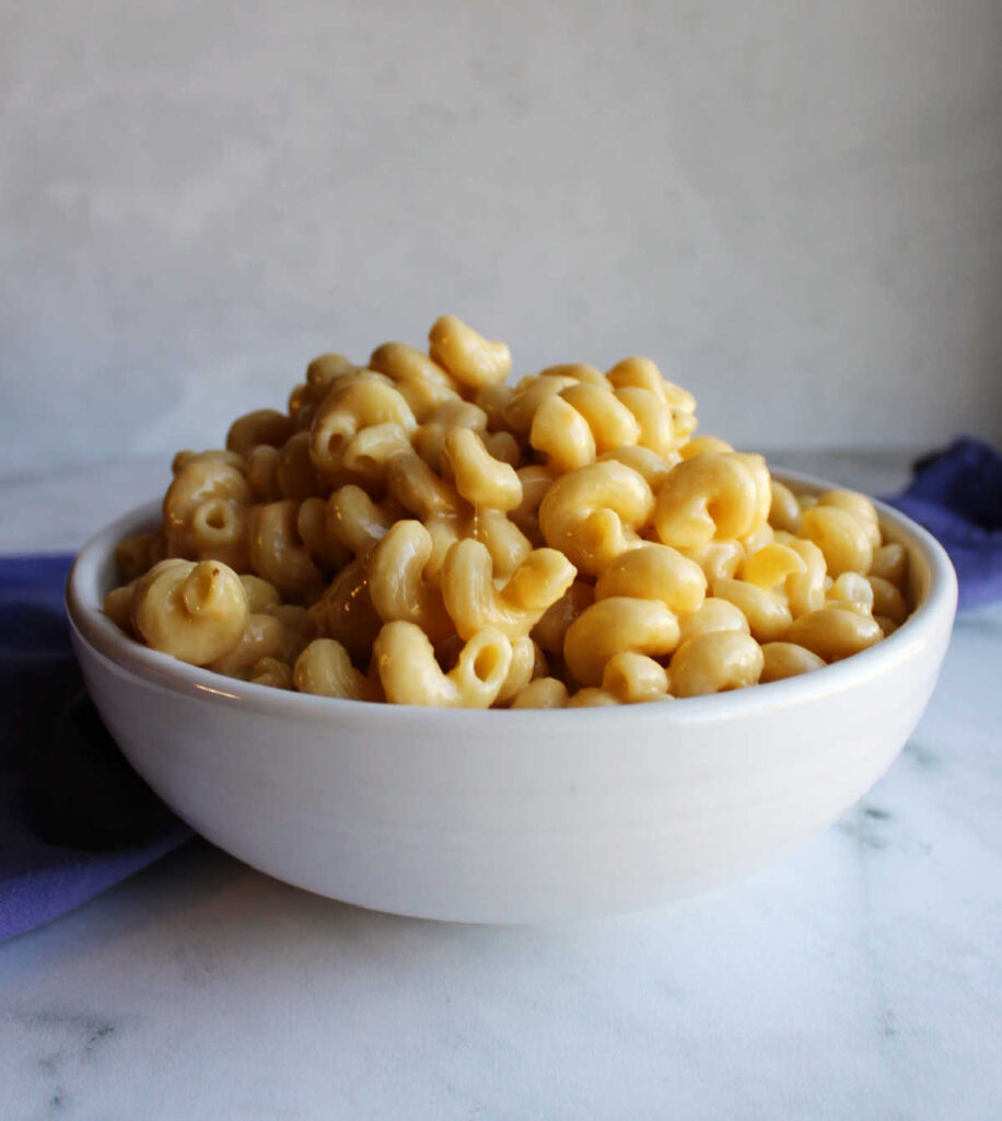 White bowl filled with curly pasta and cheese sauce.