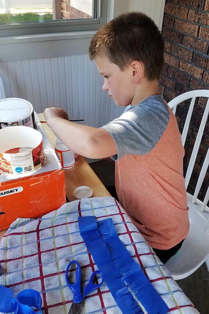 Boy putting tissue paper strips on homemade lego pinata.