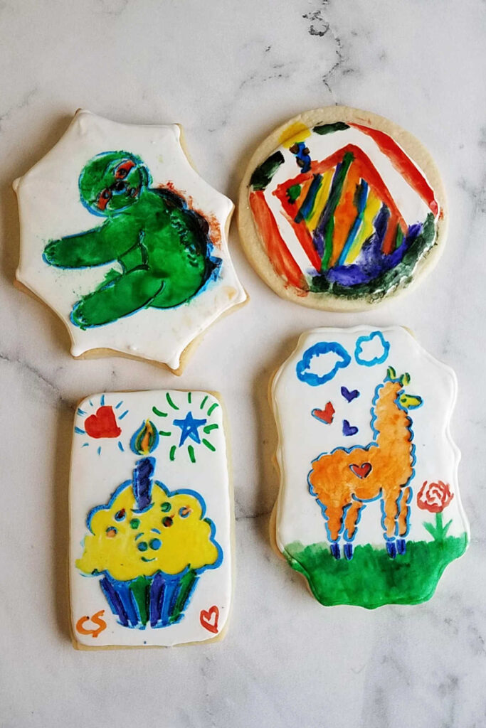 Sugar cookies with edible watercolor decorations painted on top, ready to eat.