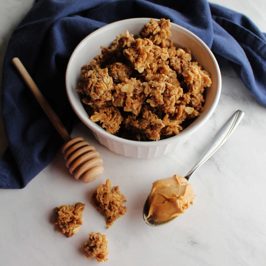 bowl of peanut butter granola next to a spoon of peanut butter and a honey drizzler.
