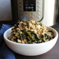 bowl of farro with kale, Italian sausage, white beans and Parmesan cheese in front of instant pot.