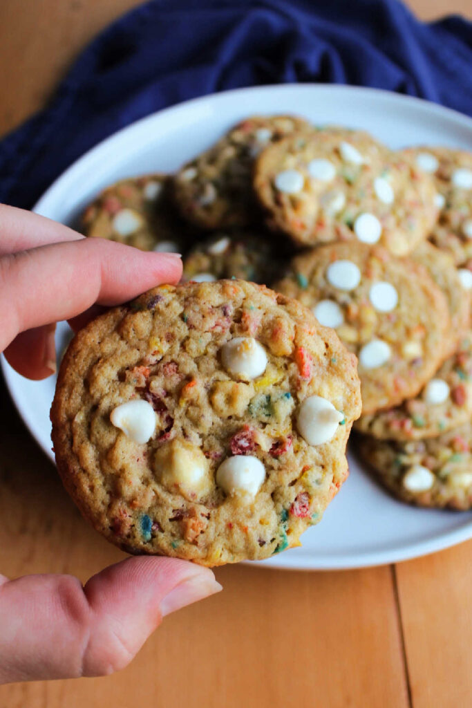 Hand holding fruity pebble cookie.