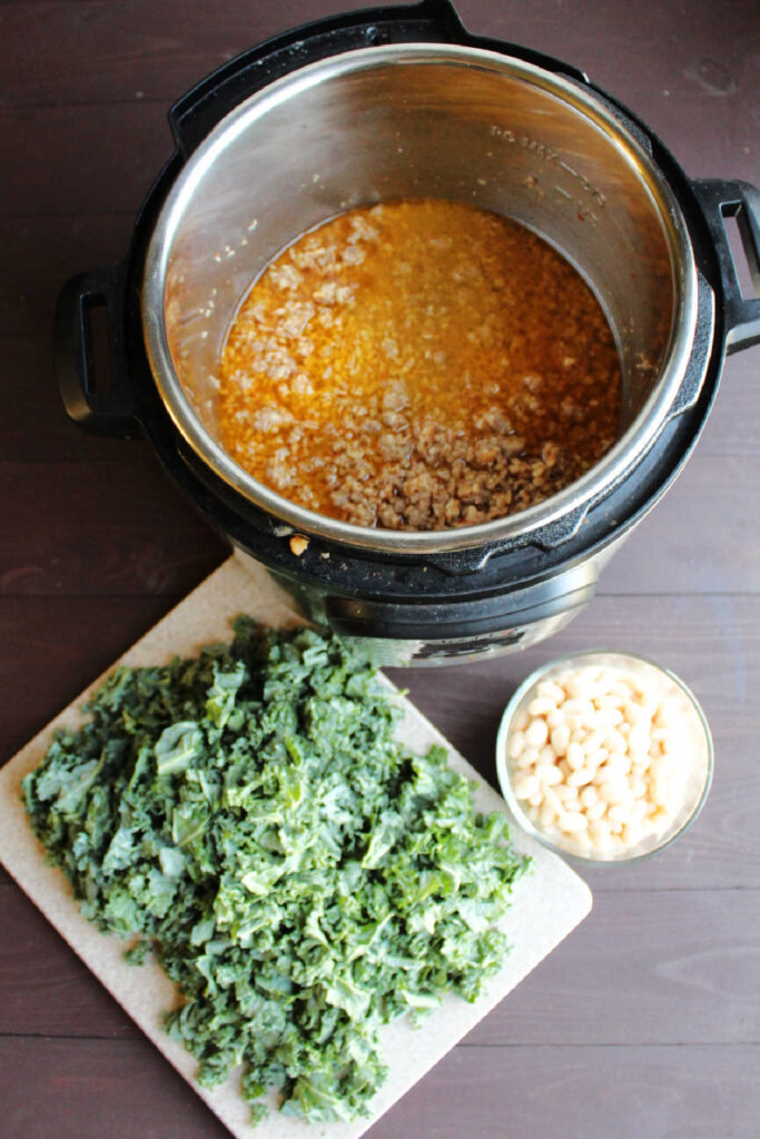 Cooked farro and sausage in instant pot next to chopped kale and bowl of beans.