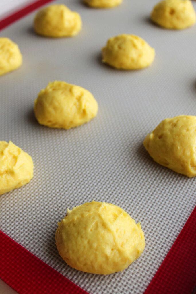 Scoops of lemon whoopie pie batter on pan ready to bake.