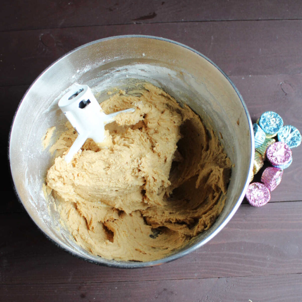 mixer bowl of peanut butter cookie dough next to pile of peanut butter cups.
