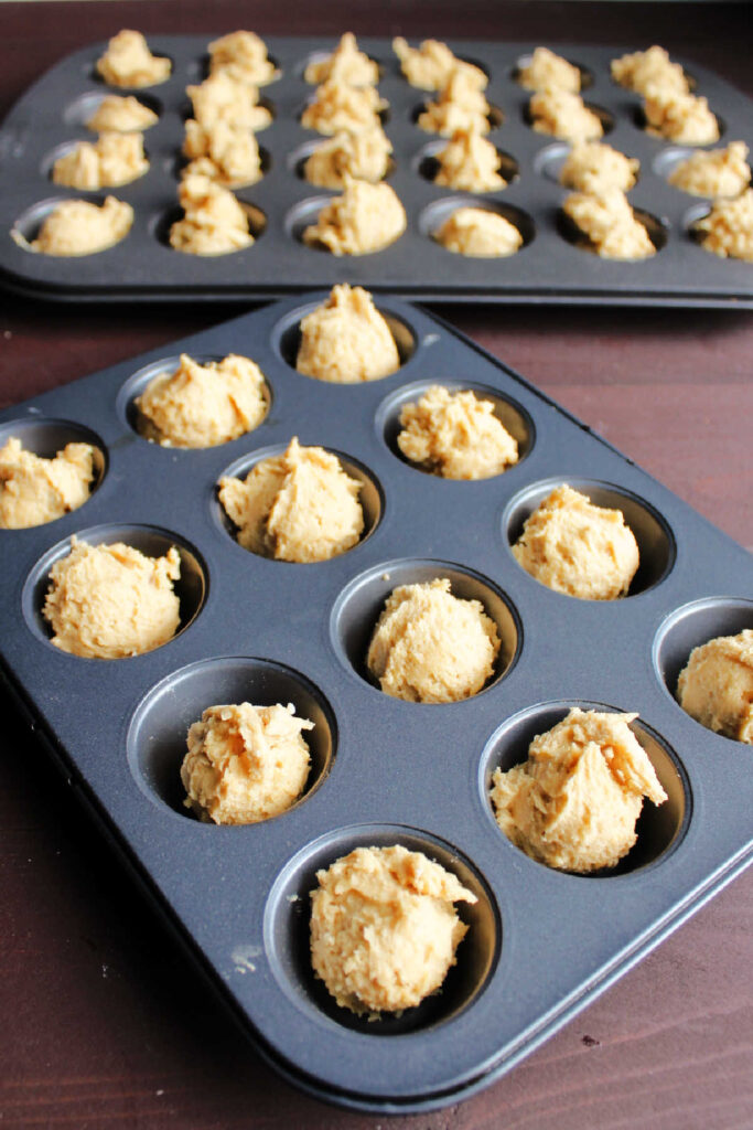 peanut butter cookie dough in mini muffin tins ready to bake