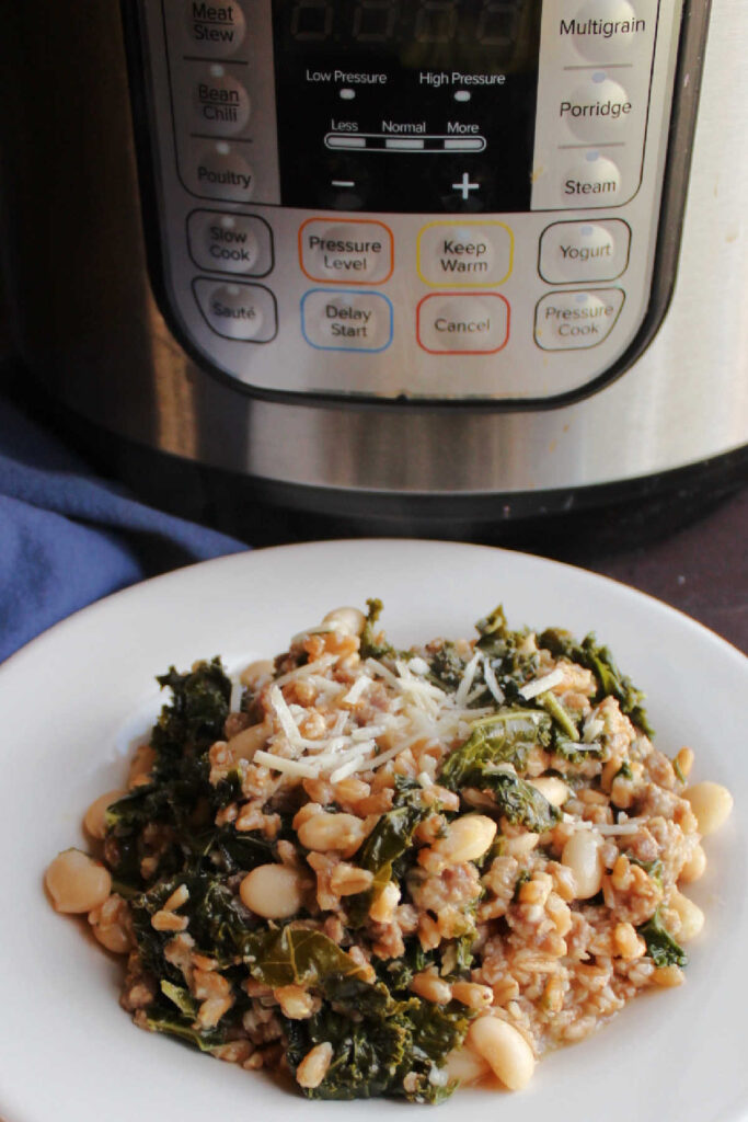 Plate of farro with Italian sausage, kale, white beans and Parmesan cheese in front of pressure cooker.