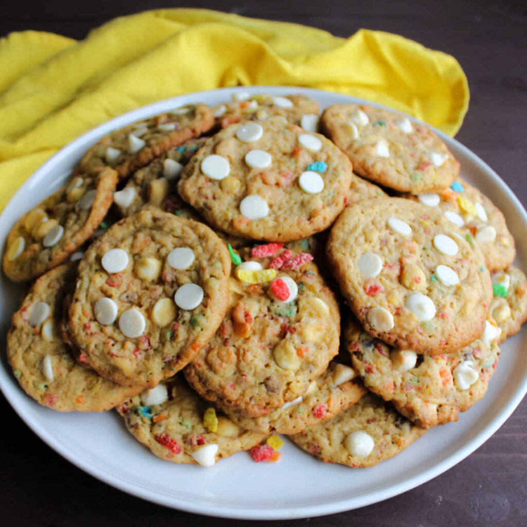 Plate piled high with fruity pebble cookies with white chocolate chips.