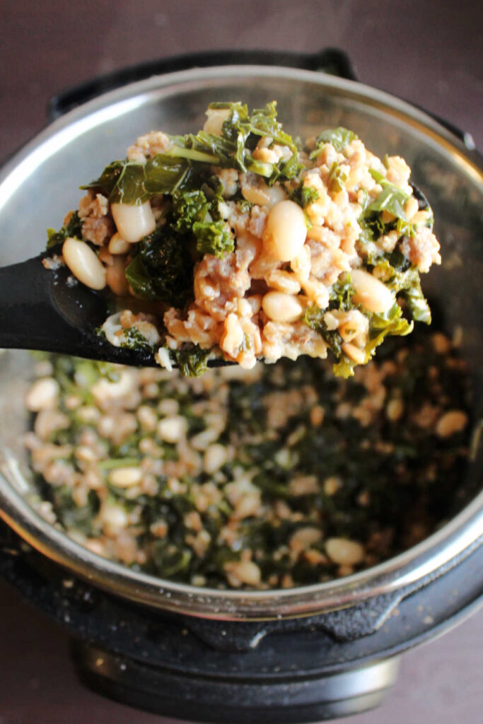 Spoonful of farro with kale and sausage being lifted out of instant pot.