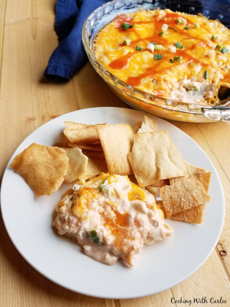 Serving of warm melty buffalo chicken dip on plate with pita chips in front of pan of remaining dip.