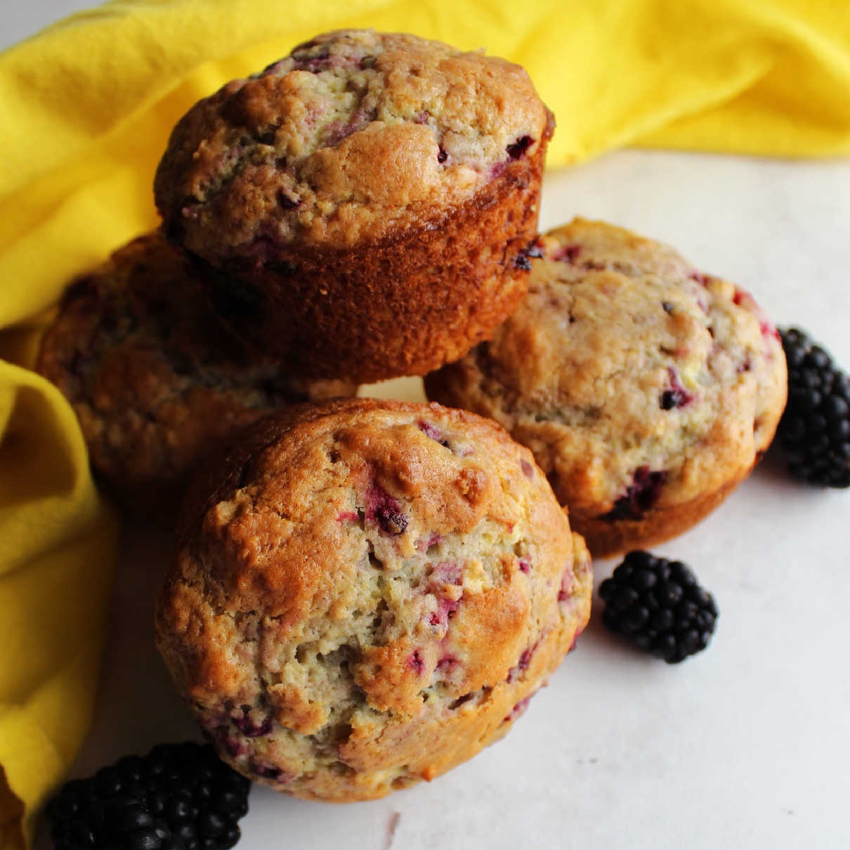 Close stack of golden blackberry muffins ready to eat.