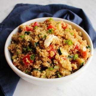 bowl of Mediterranean quinoa salad with tomatoes, cucumbers, feta and parsley.