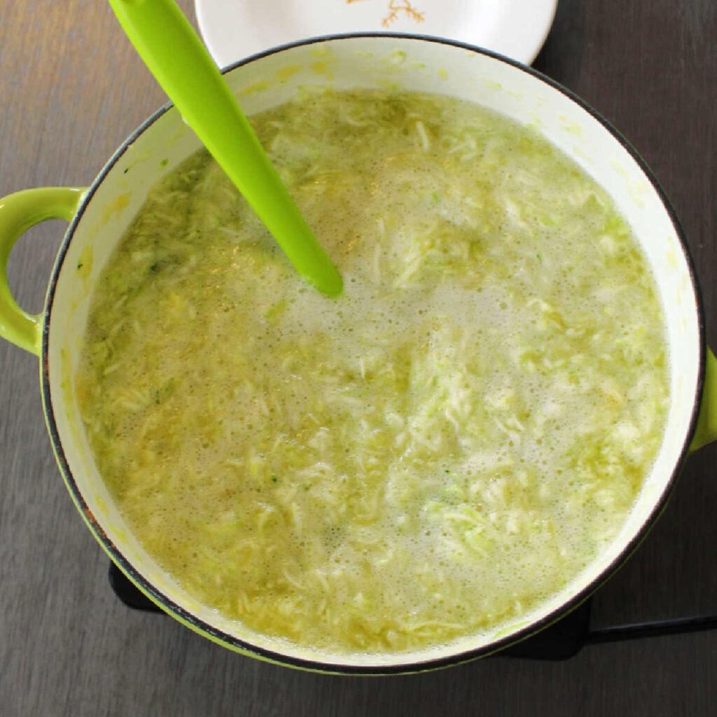 shredded zucchini, pineapple, sugar and lemon juice cooking in saucepan.